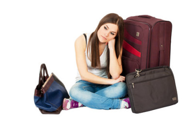Young woman waiting for yer flight with her baggage isolated on white background