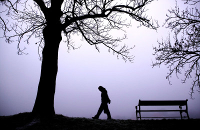 A person walking alone in thick fog.
