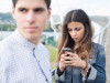 Woman distracted looking at her smart phone. The woman is not aware of her boyfriend.